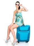 Mujer de ?asual que se coloca con la maleta del viaje Imagen de archivo libre de regalías