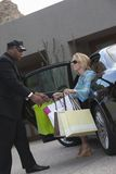 Mujer de ayuda del chófer con los bolsos de compras Imágenes de archivo libres de regalías