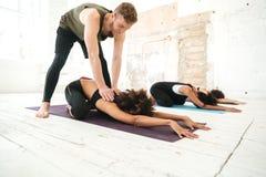 Mujer de ayuda del instructor de sexo masculino de la yoga a estirar foto de archivo libre de regalías