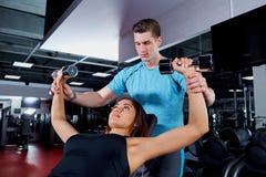 Mujer de ayuda del instructor personal que trabaja con pesas de gimnasia Fotografía de archivo libre de regalías