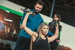Mujer de ayuda del instructor personal que trabaja con pesas de gimnasia imagen de archivo