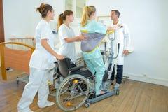 Mujer de ayuda del personal médico a la colocación imagen de archivo