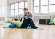 Mujer de ayuda del terapeuta físico más vieja en el gimnasio Imagen de archivo