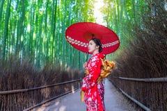 Mujer de bambú de Forest Asian que lleva el kimono tradicional japonés en el bosque de bambú en Kyoto, Japón Fotos de archivo libres de regalías