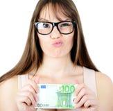 Mujer de Beauitful que lleva a cabo una cierta nota euro de la moneda con mirada divertida Imagen de archivo libre de regalías