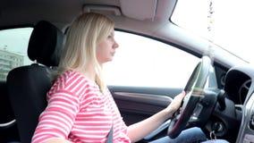 Mujer de Blondie que conduce un coche con la caja de cambios manual almacen de metraje de vídeo