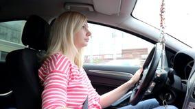 Mujer de Blondie que conduce un coche con la caja de cambios manual almacen de video