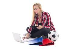 Mujer de Blondie que se sienta con el ordenador portátil, las carpetas e isola del balón de fútbol Imagen de archivo libre de regalías