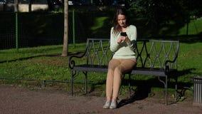 Mujer de Brunnete que se sienta en banco en el parque que comunica en smartphone metrajes