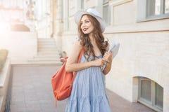 Mujer de Cheeful con la mochila y el libro que camina en la ciudad Imagen de archivo
