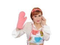 Mujer de cocinar hermosa en guante del delantal y de la cocina Imagenes de archivo
