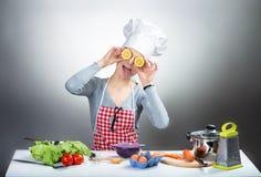 Mujer de cocinar loca con los ojos del limón Imagen de archivo