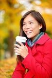 Mujer de consumición del café en caída del otoño que disfruta de caída Imagen de archivo libre de regalías