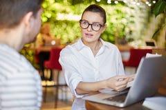 Mujer de Coworking con el hombre que usa el ordenador portátil imagen de archivo
