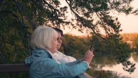 Mujer de dos ancianos que mira smartphone el paseo del otoño en paisaje del árbol y del lago almacen de video