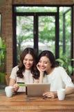 Mujer de dos asiáticos que usa el ordenador portátil para hacer compras en línea con el coche del crédito Imágenes de archivo libres de regalías