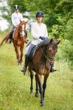 Mujer de dos jinetes en los caballos que van abajo de la colina Imagenes de archivo