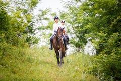 Mujer de dos jinetes en los caballos que van abajo de la colina Fotografía de archivo