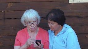 Mujer de dos mayores que mira el teléfono móvil y el hablar al aire libre en campo almacen de metraje de vídeo