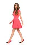 Mujer de Elegnat que camina en Mini Dress Ans High Heels rosado fotografía de archivo