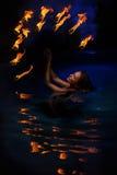 Mujer de Firedancer en agua Imagenes de archivo