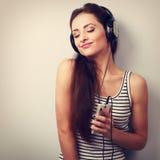 Mujer de goce feliz que escucha la música en auriculares con clos Fotos de archivo libres de regalías