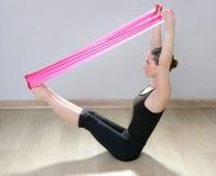 Mujer de goma roja de la gimnasia de la venda de la resistencia de la yoga de Pilates Foto de archivo libre de regalías