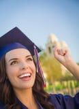 Mujer de graduación feliz de la raza mixta en casquillo y vestido Imágenes de archivo libres de regalías