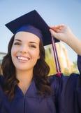 Mujer de graduación feliz de la raza mixta en casquillo y vestido Foto de archivo libre de regalías