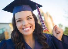 Mujer de graduación feliz de la raza mixta en casquillo y vestido Imagen de archivo libre de regalías