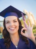 Mujer de graduación feliz de la raza mixta en casquillo y vestido Fotos de archivo libres de regalías