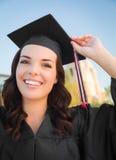 Mujer de graduación feliz de la raza mixta en casquillo y vestido Imagenes de archivo