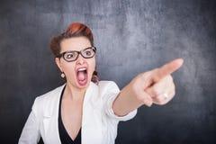 Mujer de griterío enojada que señala en fondo de la pizarra imagenes de archivo