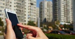 mujer de 4k A que usa un smartphone contra fondo del edificio del negocio almacen de metraje de vídeo