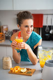 Mujer de la aptitud con el smoothie de la calabaza en cocina Foto de archivo