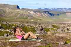 mujer de la aptitud de Sentar-UPS que hace flexiones de brazos afuera Imagen de archivo libre de regalías