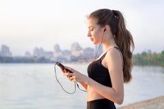 Mujer de la aptitud en el lago que escucha la música en el teléfono celular Fotografía de archivo libre de regalías
