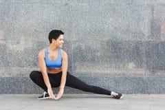 Mujer de la aptitud en estirar el entrenamiento al aire libre Imagen de archivo libre de regalías
