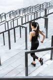 Mujer de la aptitud en la ropa de deportes que corre abajo en las escaleras del estadio Fotos de archivo libres de regalías