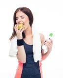 Mujer de la aptitud que come la manzana y que sostiene la botella con agua Imagen de archivo libre de regalías