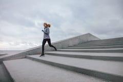 Mujer de la aptitud que corre abajo en pasos Imagen de archivo