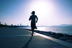 mujer de la aptitud que corre en la playa de la salida del sol Imagenes de archivo