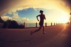 Mujer de la aptitud que corre en rastro de la playa de la salida del sol Imagen de archivo