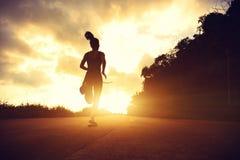 Mujer de la aptitud que corre en rastro de la playa de la salida del sol Foto de archivo libre de regalías