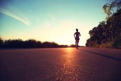 Mujer de la aptitud que corre en rastro de la playa de la salida del sol Imagenes de archivo