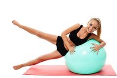 Mujer de la aptitud que hace aeróbicos con una bola del gimnasio Imágenes de archivo libres de regalías