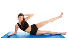 Mujer de la aptitud que hace aeróbicos en la estera de la gimnasia Imágenes de archivo libres de regalías