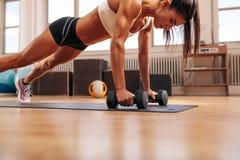Mujer de la aptitud que hace ejercicio de los pectorales con pesas de gimnasia Imagen de archivo