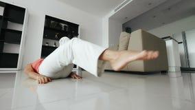 Mujer de la aptitud que hace ejercicio del pie en piso y que aumenta la pierna para arriba en el entrenamiento casero almacen de metraje de vídeo