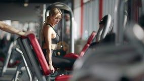 Mujer de la aptitud que hace ejercicio en el simulador del deporte en club de deporte almacen de video